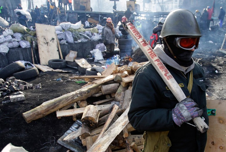 A protester guards the barricade in front of riot police in Kiev, Ukraine, Monday, Jan. 27, 2014. Ukraine's justice minister is threatening to call for a state of emergency unless protesters leave her ministry building, which they occupied during the night. The seizure of the building early Monday underlined how anti-government demonstrators are increasingly willing to take dramatic action as they push for the president's resignation and other concessions.