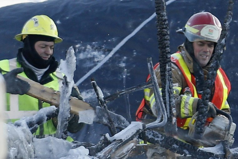 Image: A firefighter cuts debris with a chainsaw while he works at the site of Residence du Havre in L'Isle Verte