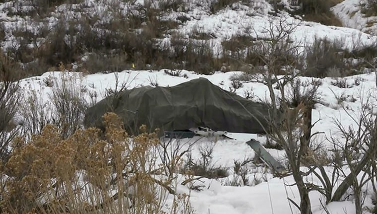 Image: A tarp covers the wreckage of a helicopter that crashed near Silt, Colo.