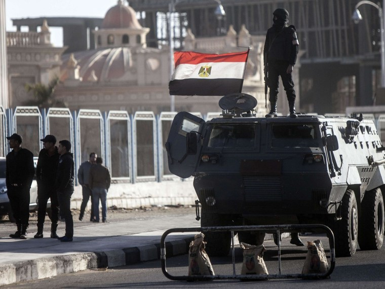 Image: Egyptian riot policemen stand guard outside the police building in Cairo where a new hearing in the trial of deposed president Mohamed Morsi opened Tuesday.