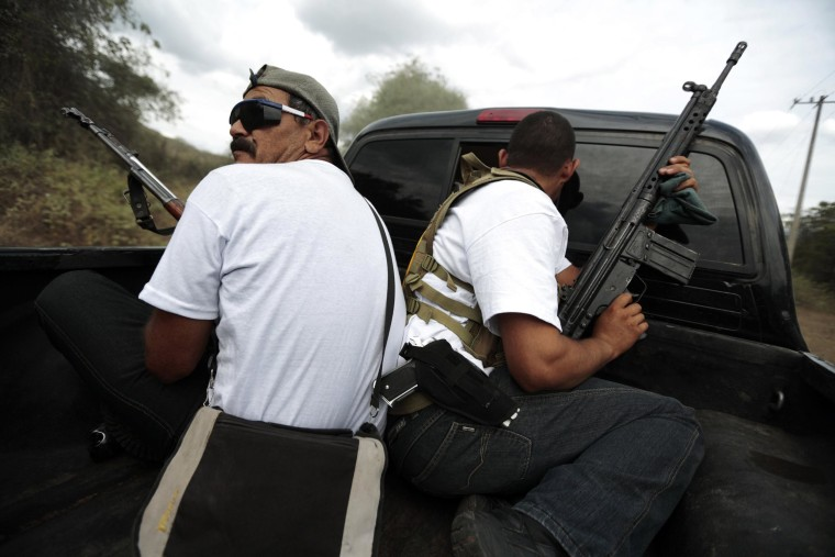Image: Vigilantes ride on the back of a pick-up truck while driving in a convoy to Poturo