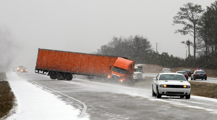 Image: A truck goes off the road into the median while trying to avoid another wrecked truck as snow begins to accumulate on I-65 in Alabama on Tuesday, Jan. 28 in Clanton, Ala.