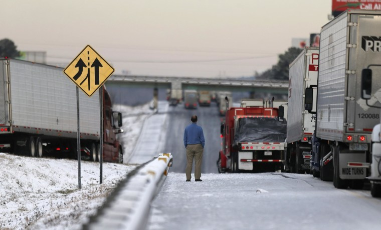 Image: A man stands on the frozen roadway as he waits for traffic to clear along Interstate 75 Wednesday, Jan. 29, 2014, in Macon, Ga.