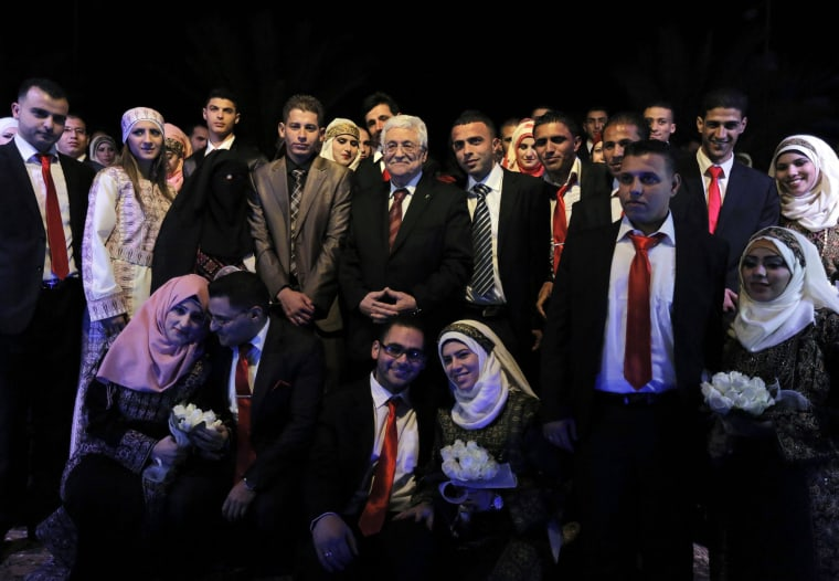 Image: Palestinian couples pose for pictures with Palestinian President Mahmoud Abbas during a mass wedding ceremony in the West Bank city of Jericho