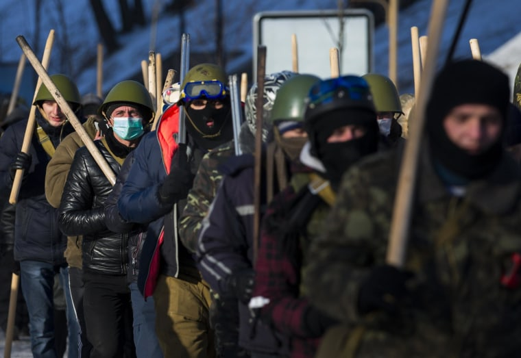 Image: Members of various anti-government paramilitary groups march along street during show of force in Kiev