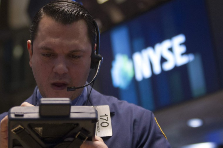 Trader on the floor of the New York Stock Exchange on Wednesday. The Dow fell almost 200 points as the Federal Reserve said it will cut another $10 billion from its stimulus package.