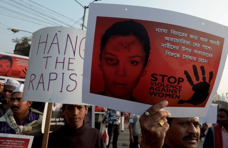 Image: Activists hold posters during a rally as they protest against the gang-rape and murder of a teenager
