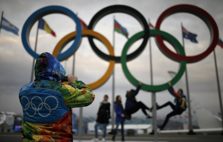 Image: Olympic volunteer takes pictures of people as they pose under the Olympic rings, as preparations continue at the Olympic Park for the Sochi 2014 Winter Olympics