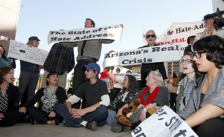 Immigration rights protesters sit out in front of the House of Representatives after Arizona Gov. Jan Brewer gives her State of the State address at the Arizona Capitol Monday, Jan. 13, 2014, in Phoenix.