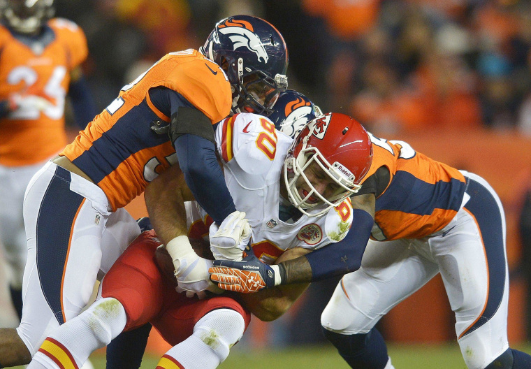 Image: Two linebackers tackle a tight end.