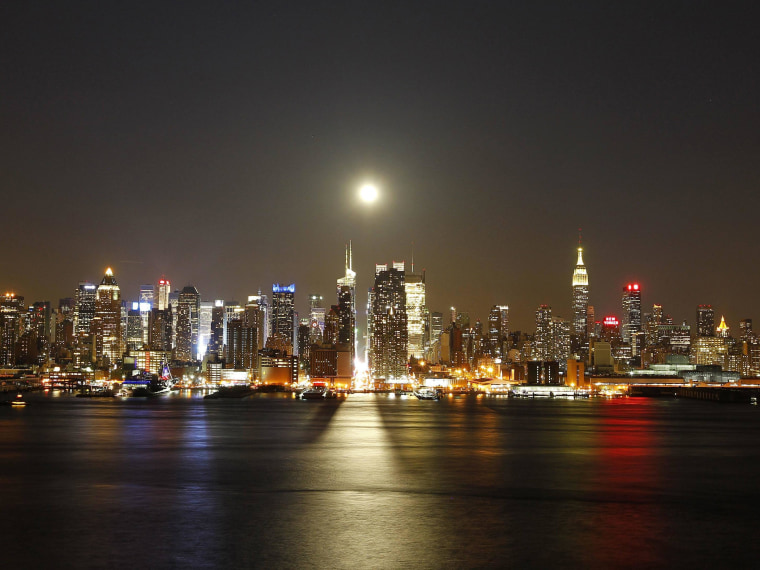 Image: A full moon rises over New York City above 42nd Street, as seen across the Hudson River in Weehawken, NJ.