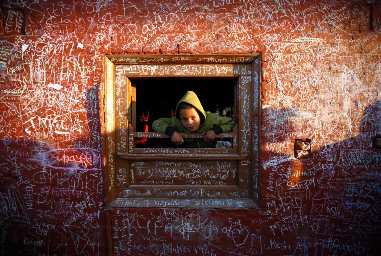 Image: A boy looks through the window of the Saraswati temple, whose walls are filled with writings, during the Shreepanchami festival in Kathmandu