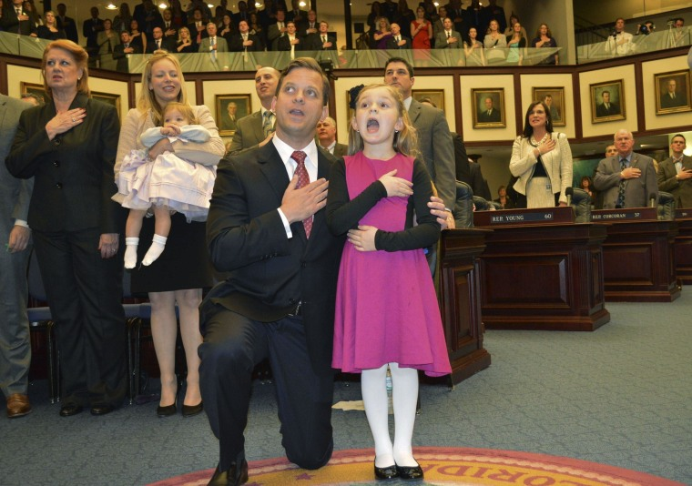 Image: Florida Lieutenant Governor Lopez-Cantera kneels next to his six-year-old daughter, Sabrina, as she leads the Pledge of Allegiance on the House of Representatives floor in Tallahassee