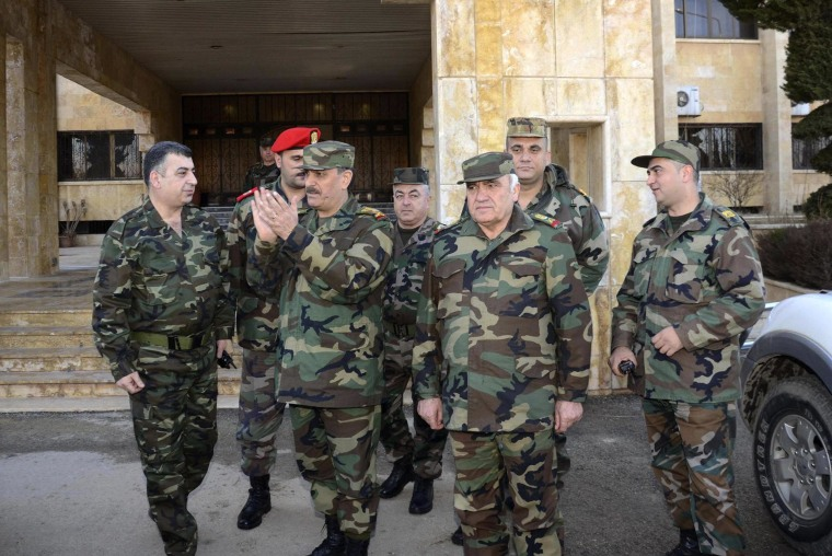 Image: Syrian Defence Minister Fahd al-Freij gestures as he walks while visiting military bases and meets with officers in Aleppo