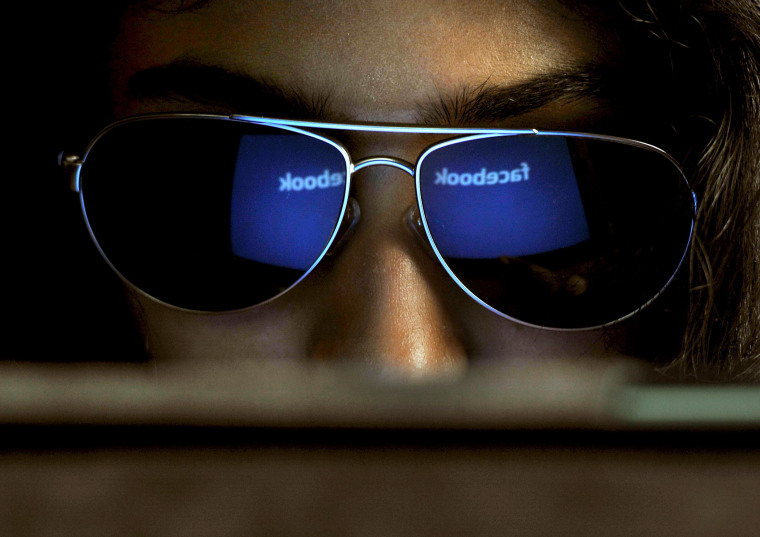 In this photograph taken on May 15, 2012, The 'Facebook' logo is reflected in a young Indian woman's sunglasses as she browses on a tablet in Bangalore.