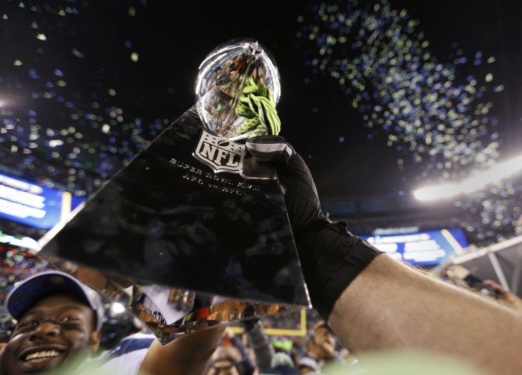 Image: Seattle Seahawk players celebrate with the Vince Lombardi trophy after defeating the Denver Broncos in the NFL Super Bowl XLVIII in East Rutherford