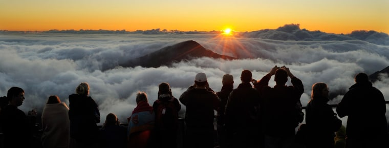 Visitors watch the sun rise at 10,000 feet in Haleakala National Park in Maui, Hawaii.