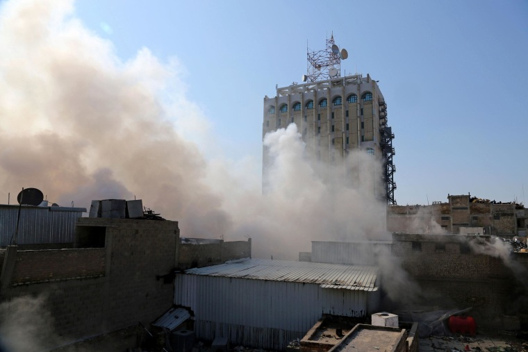 Image: Smoke rises after a car bomb went off at a commercial center in Khilani Square in central Baghdad