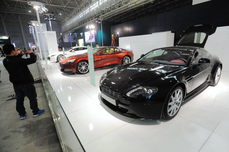 Image: Visitors take photos of Aston Martin cars at an auto show in Wuhan, China
