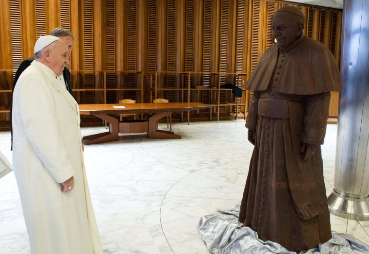 Image: Pope Francis looks at a chocolate statue made in his likeness, which he received as a gift, in Paul VI's Hall at the Vatican