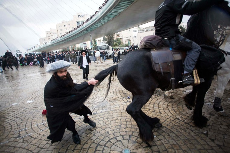 Image: An ultra-Orthodox Jewish protester pulls the tail of a horse used by policemen to disperse protesters during a demonstration in Jerusalem