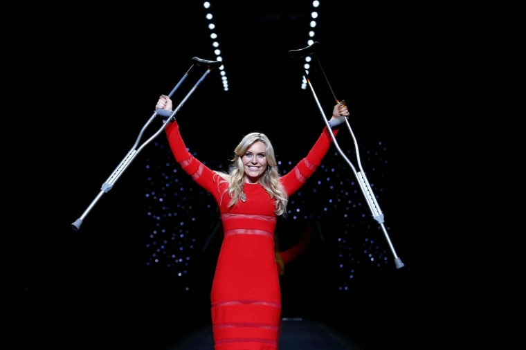 Olympic downhill champion Lindsey Vonn raises her crutches as she presents a creation by Cynthia Rowley for the The Heart Truth Fall 2014 collection during New York Fashion Week February 6, 2014.