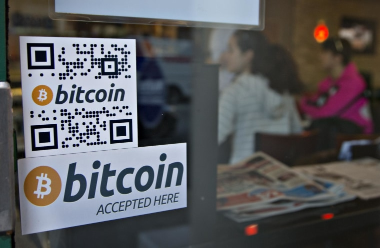 Signs on window advertise a bitcoin ATM machine that has been installed in a Waves Coffee House in Vancouver, British Columbia.