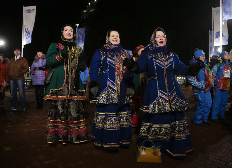 Three women in traditional Russian costumes dance as they watch the live broadcast of the opening ceremony of the 2014 Winter Olympics on Feb. 7 in Krasnaya Polyana, Russia.