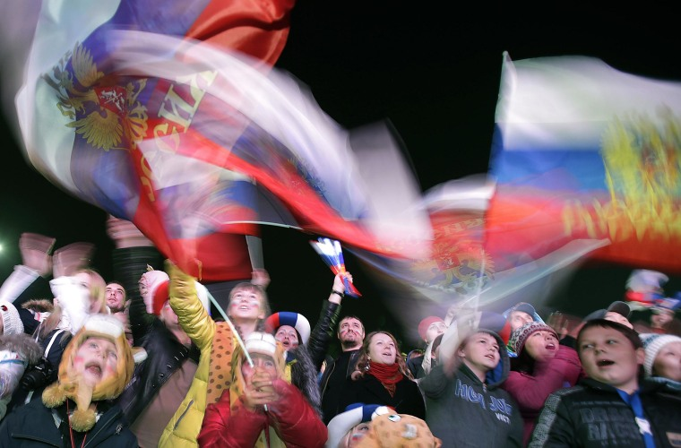 Russian families gather and wave their national flag during the national anthem as they watch the live telecast of the 2014 Winter Olympics opening ceremony on Feb. 7 in downtown Sochi, Russia.