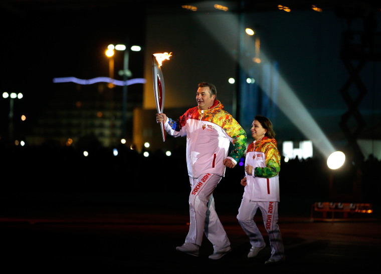 Irina Rodnina and Vladislav Tretyak approach the the Olympic cauldron as they prepare to light it during the opening ceremony of the 2014 Winter Olympics in Sochi, Russia, Friday, Feb. 7, 2014.