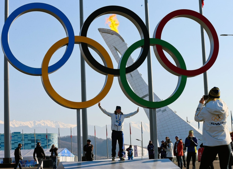 A visitor poses in front of the Olympic rings at the Sochi Olympic Park on Saturday.