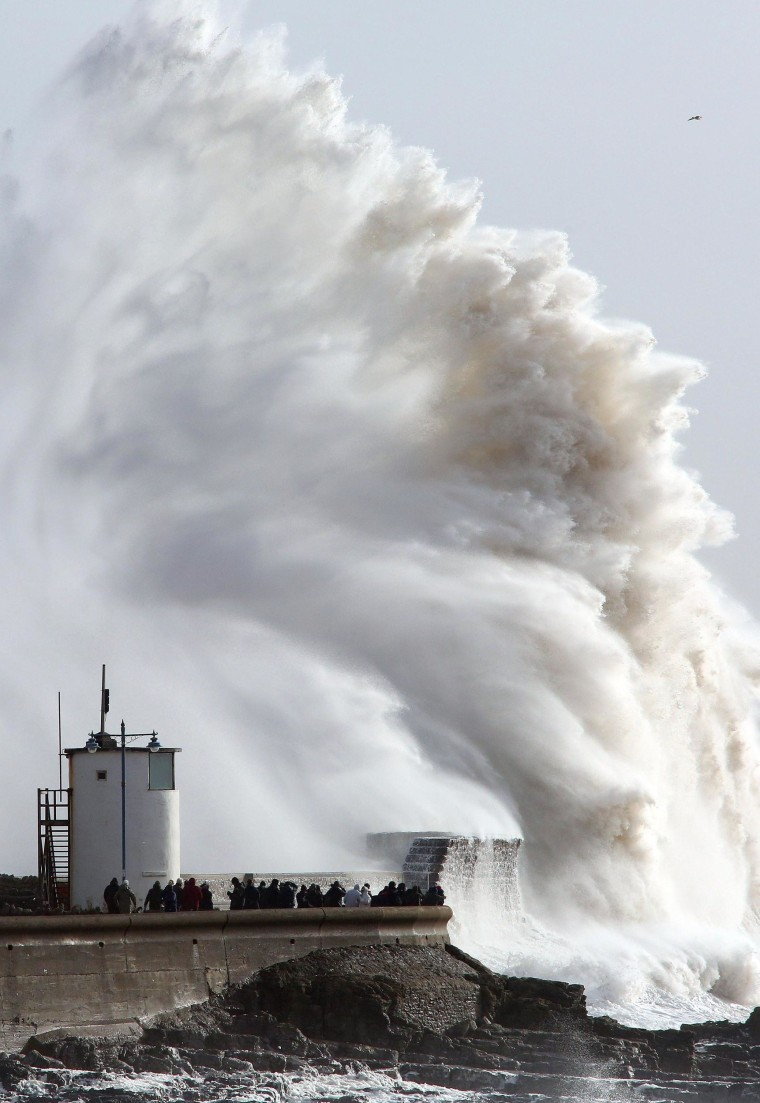 Image: People look on as high waves strike the harbour wall at Porthcawl, south Wales