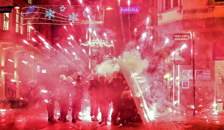 Turkish riot police takes cover behind their shields as fireworks shot by protesters explode in front of them.