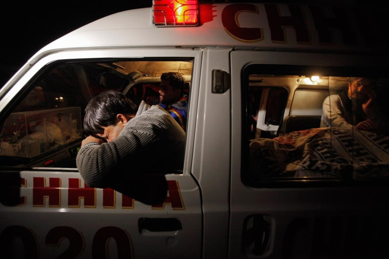 Image: A relative mourns his family member, who was killed by unknown gunmen, next to his body in an ambulance, in Karachi.
