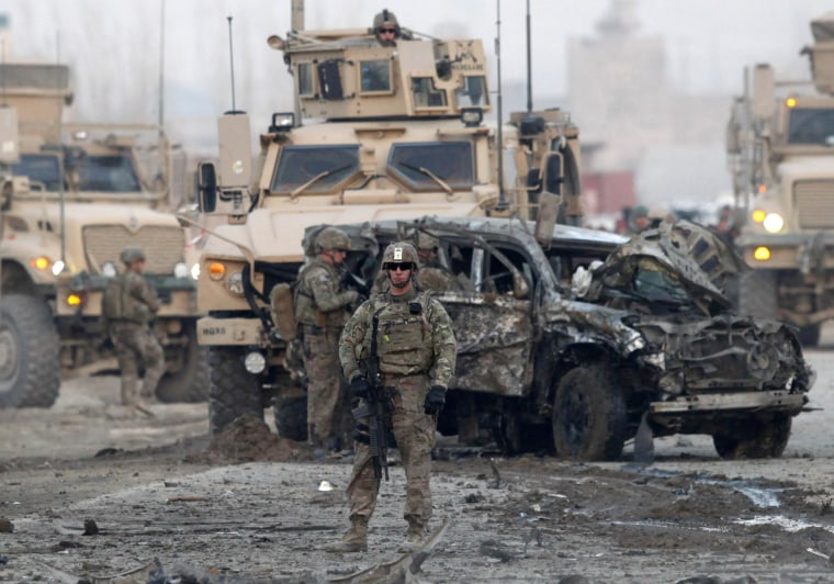 Image: U.S. troops stand guard at the site of a suicide car bomb attack in Kabul