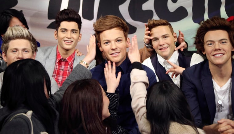 Fans touch wax figures of One Direction members Louis Tomlinson, center, and Liam Payne, second from right, during an unveiling ceremony at Madame Tussauds in Tokyo, Tuesday, Feb. 11, 2014. (AP Photo/Koji Sasahara)