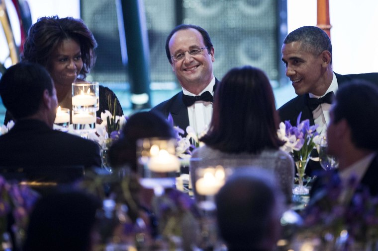 U.S. First Lady Michelle Obama, left, French President Francois Hollande, centr and U.S. President Barack Obama talk with guests during a State Dinner at the White House February 11, 2014 in Washington, DC. The Obamas hosted Hollande for a State Dinner during the second day of the French President's three-day visit to the United States.