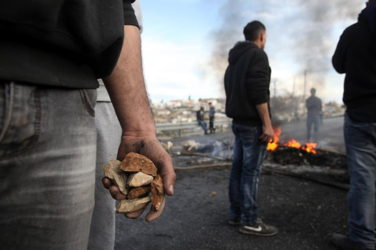 Image: A Palestinian protester holds stones during clashes with Israeli soldiers