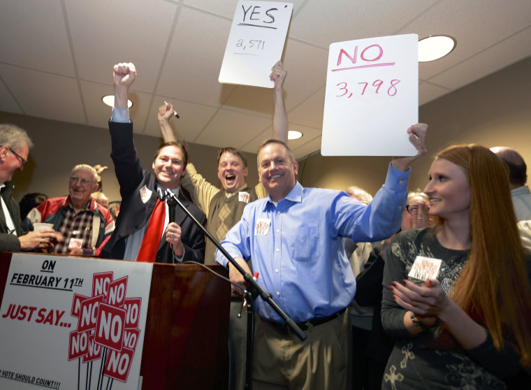 State Sen. Charlie Janssen of Fremont, third left, Jeremy Jensen, center, and John Wiegert, second right, celebrate in Fremont, Neb., Tuesday, Feb. 11, 2014, after city voters have decided by voting no, to uphold the law designed to bar immigrants from renting homes if they don't have legal permission to be in the U.S.