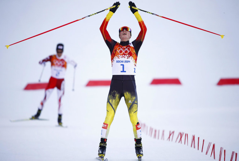 Image: Winner Germany's Frenzel celebrates as he crosses the finish line followed by second-placed Japan's Watabe during the cross country race of the Nordic Combined individual normal hill 10 km event at the Sochi 2014 Winter Olympic Games
