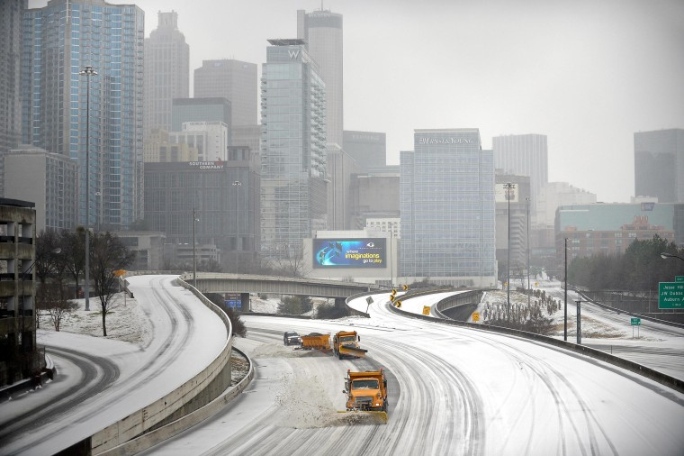 Image: Snow plows clear Interstate 75/85 on the downtown connector while transportation and business grinds to a halt during a winter storm on Wednesday in Atlanta.