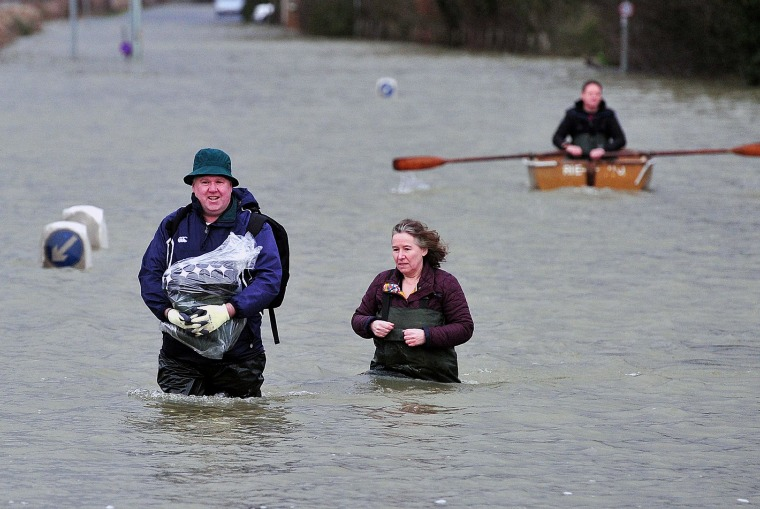 Image: A couple wade along a flooded road Wednesday near Egham, west of London.