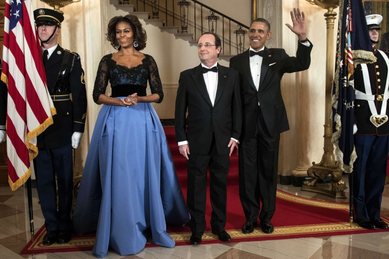 First Lady Michelle Obama, in a dress designed by Carolina Herrera, poses with President Barack Obama and French President Francois Holland for an official photo before a State Dinner at the White House February 11, 2014 in Washington, DC.