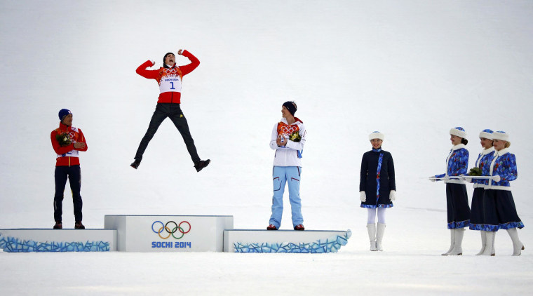 Image: Winner Germany's Frenzel jumps on the podium during the flower ceremony for the Nordic combined individual normal hill 10 km event at the Sochi 2014 Winter Olympic Games