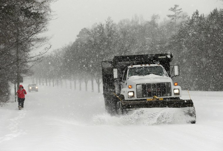 Image: A truck plows a snowy road in Charlotte, N.C.
