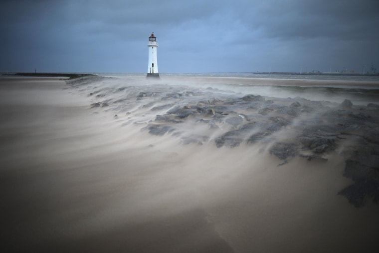 A miniature sandstorm whipped up by unusually high winds blows across the breakwater next to the Perch Rock lighthouse on February 12, 2014 in New Brighton, United Kingdom.
