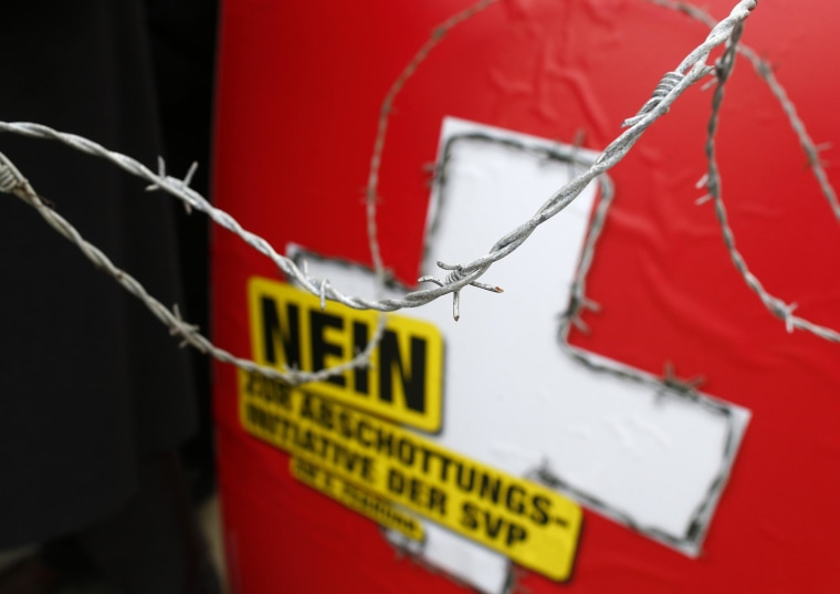 A poster against the 'mass immigration initiative' is seen through barbed wire fence on the Federal Square before a campaign in Bern January 29, 2014. Switzerland will vote February 9, 2014 on the Swiss People's Party SVP initiative whether to re-impose quotas on immigrants from the European Union.