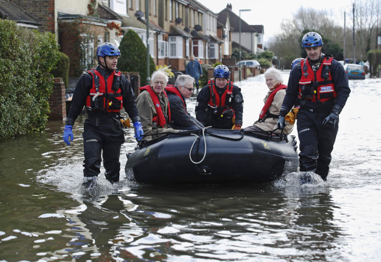 Image: Police specialist search team rescues Archie and Dorothy Doye  from their home which was surrounded by flood water at Egham after the River Thames burst its banks in south east England