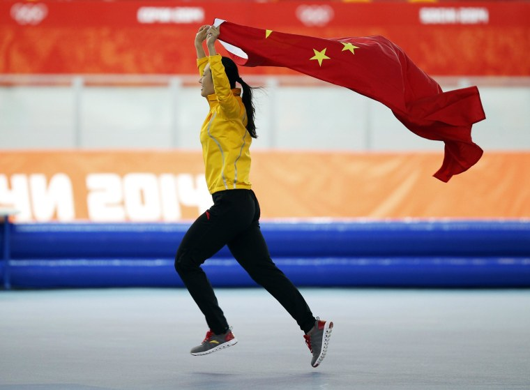 Gold medalist Zang Hong of China holds her national flag and runs in celebration after the women's 1,000-meter speed skating race during the 2014 Winter Olympics on Feb. 13.