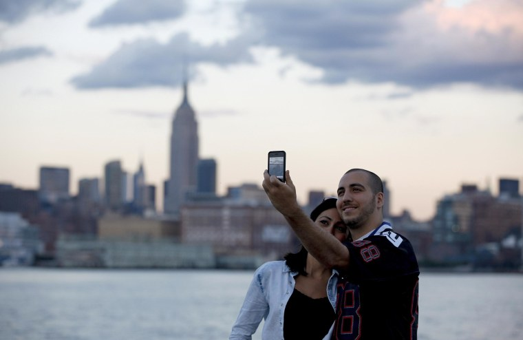 With the skyline of New York behind them, a couple takes a picture of themselves from a pier in Hoboken, N.J.